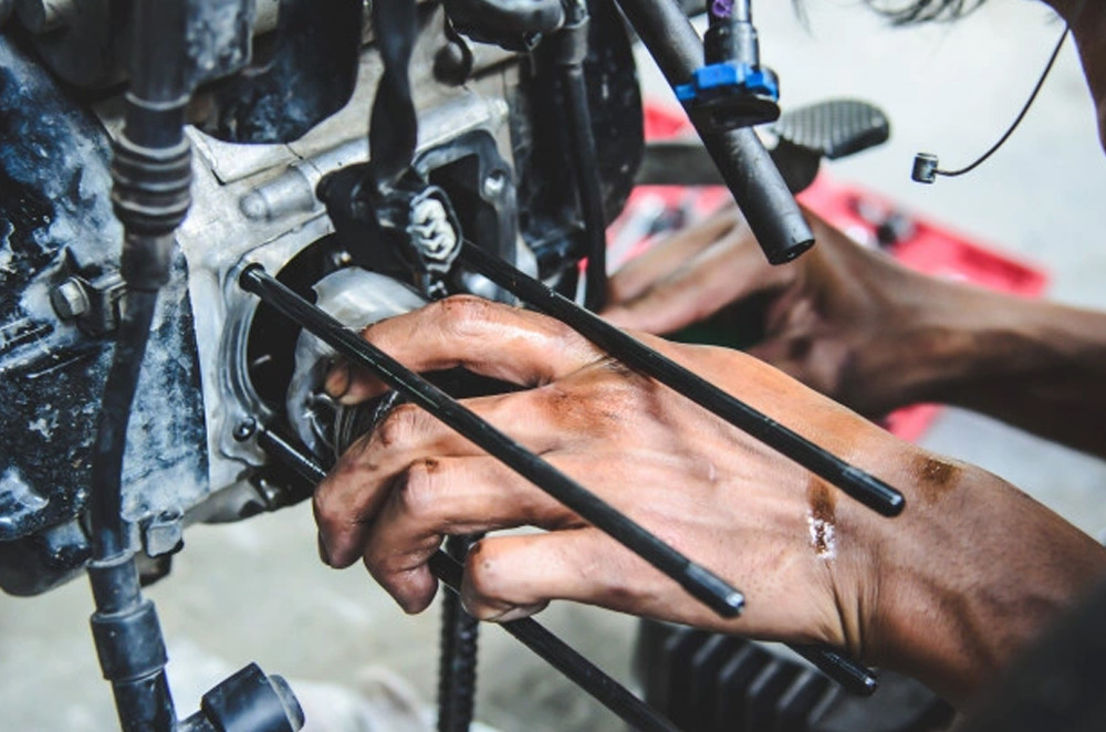 Person working on a motorcycle engine